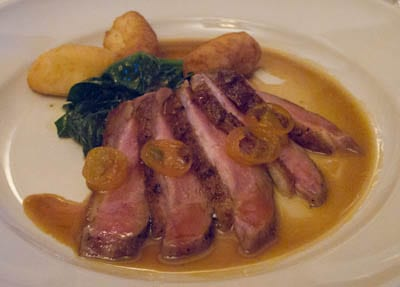 Grilled Sonoma Liberty duck breast with kumquat, pommes dauphines, and young spinach