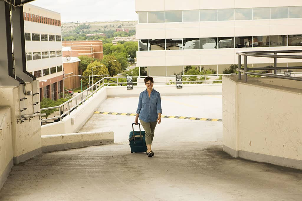 Andi Parking Garage with her suitcase