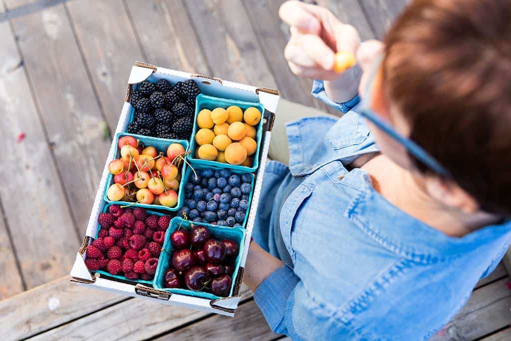 Eating fruit at the Billings Montana Yellowstone Valley Farmers Market in Chicos Summer Travel Collection