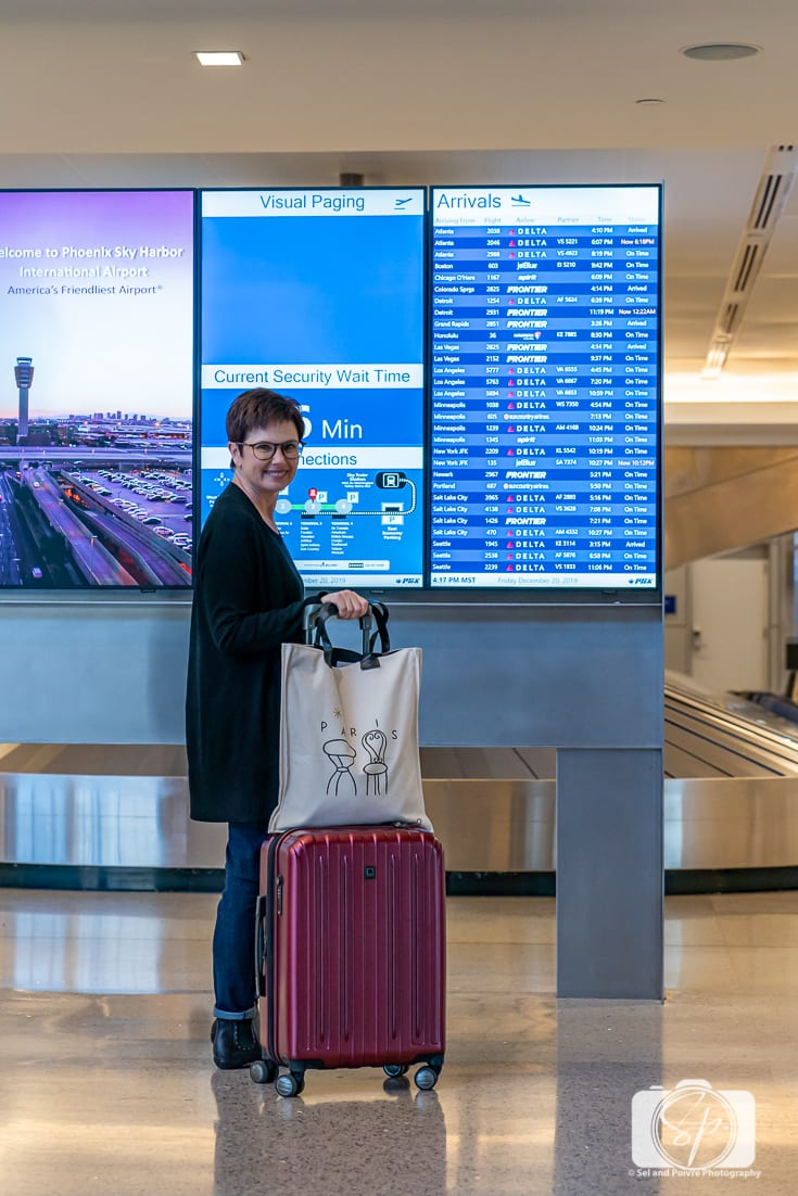 Andi with her Delsey Paris Helium Titanium hardside luggage set carry at the Arrivals panel