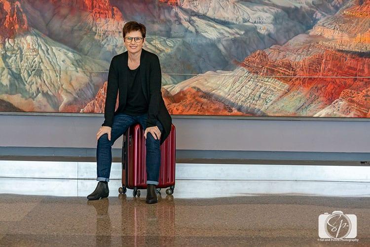Andi with her Delsey Paris Helium Titanium hardside luggage set carry on hero