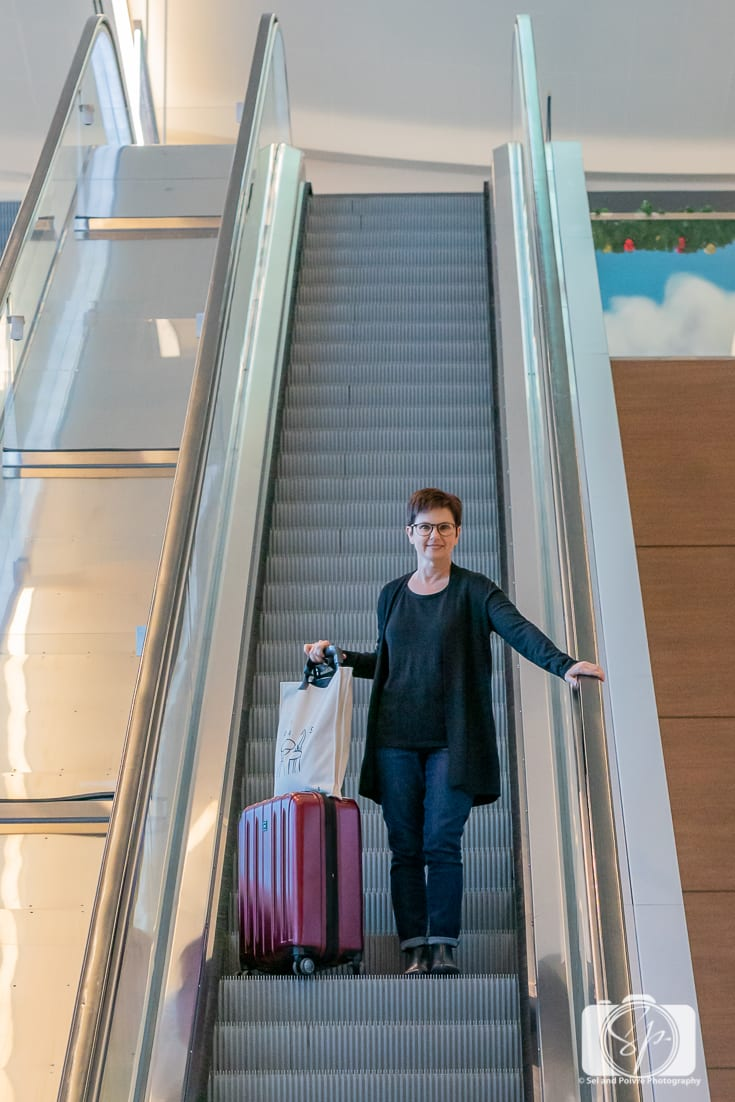 Andi with her Delsey Paris Helium Titanium hardside luggage set carry on the airport escalator