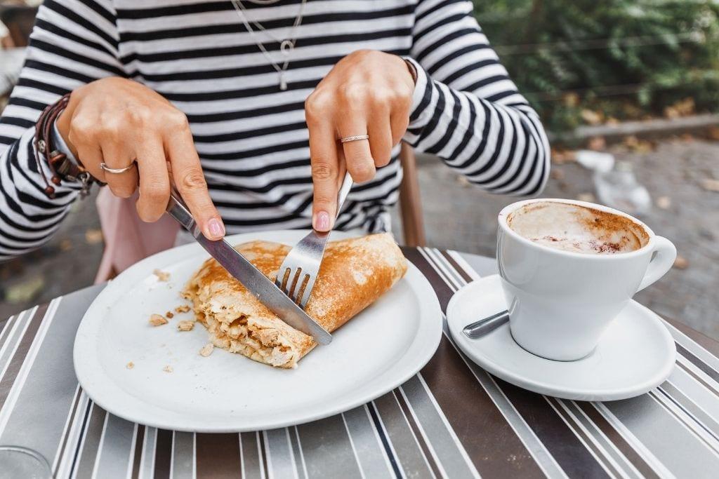 woman eating a crepe