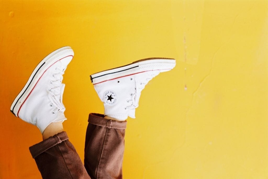 pair of converse in the air in front of yellow wall