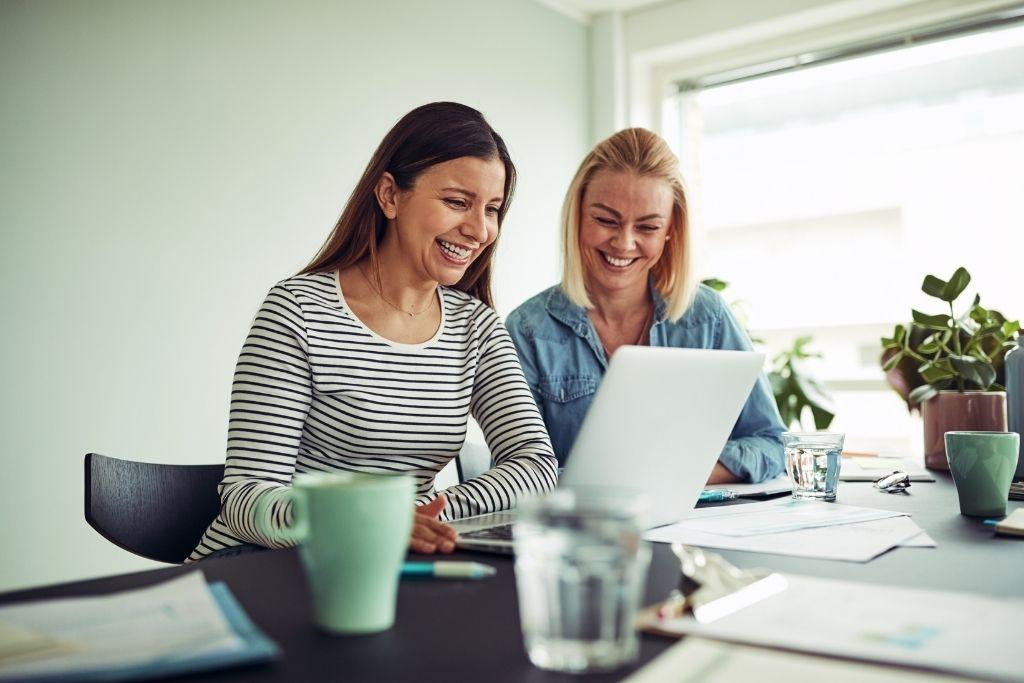 2 girls smiling at laptop