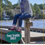 girl sitting on dock with red shoes