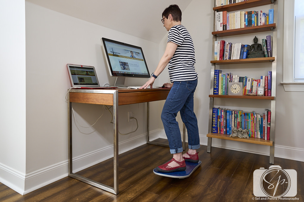 Andi standing at her desk with her FluidStance Balance Board Ocean Blue Level