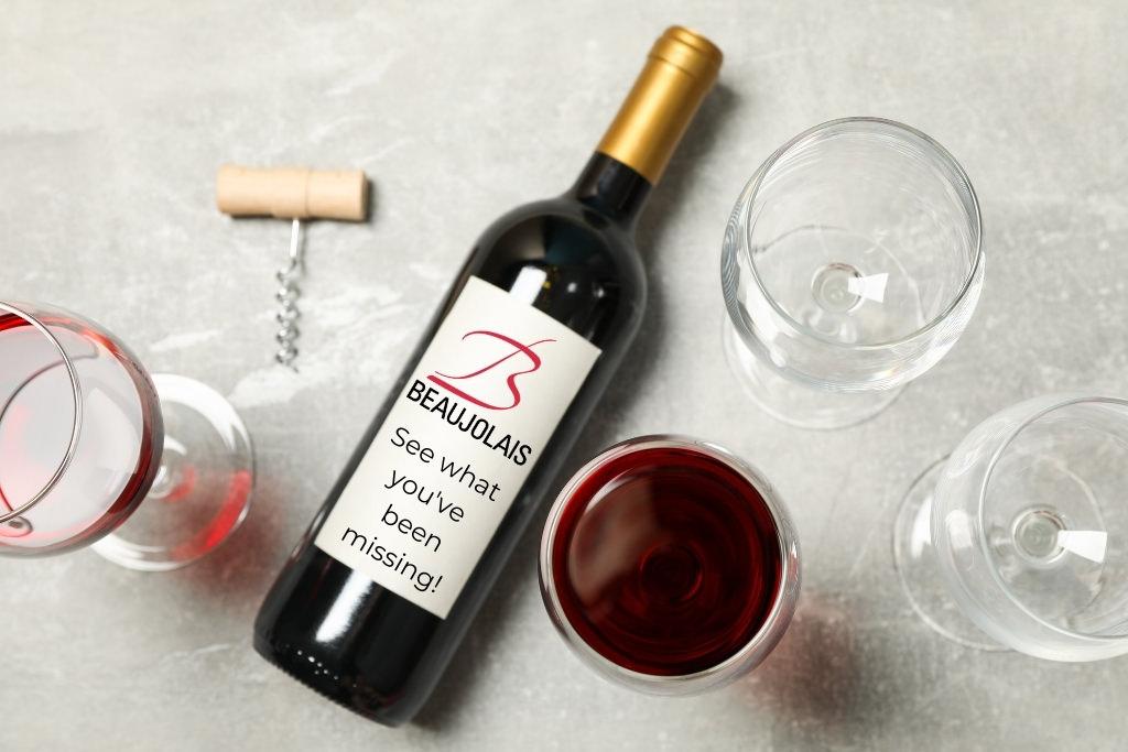 open wine bottle, glasses surrounding it