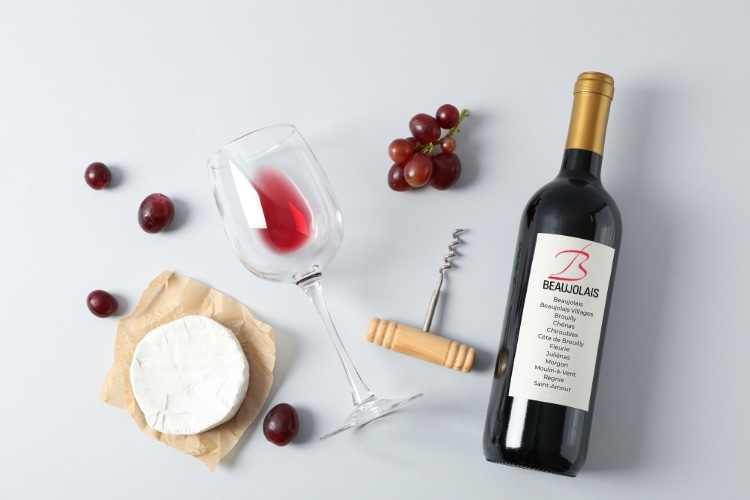red wine bottle, grapes, cheese and wine glass