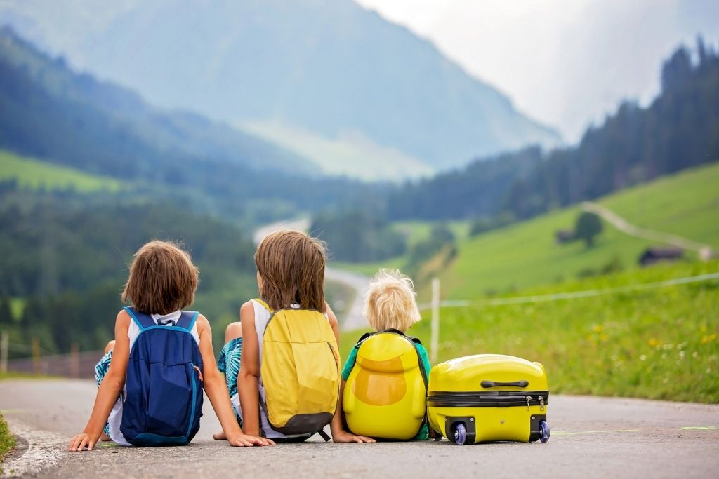 3 kids sitting on the road with backpacks