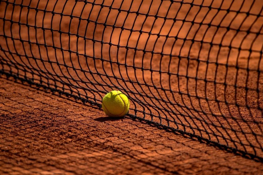 tennis ball on dirt court