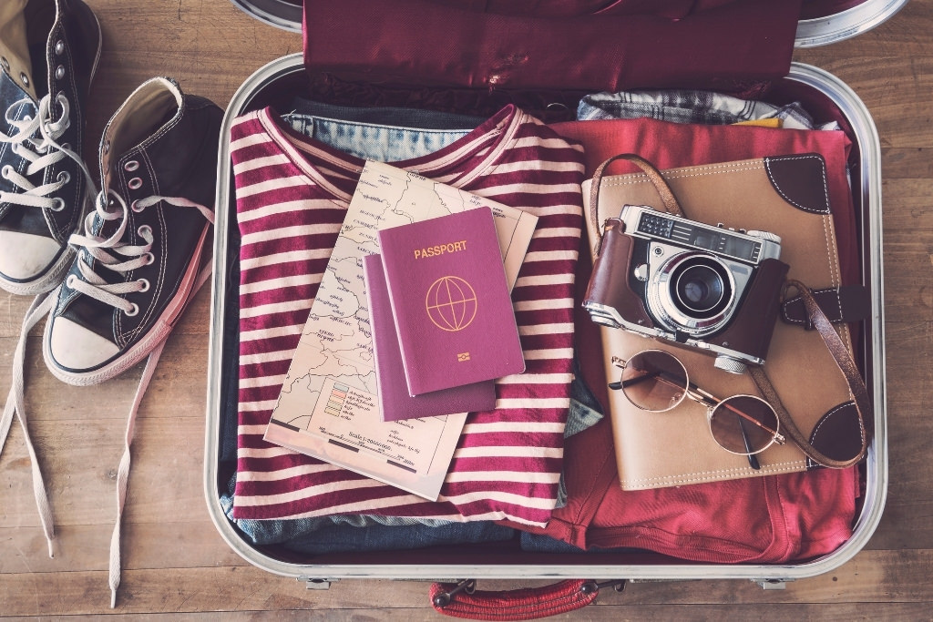 suitcase with clothes, camera, passport