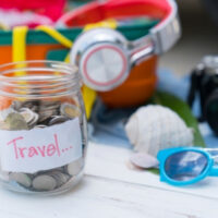 Glass jar with the word travel on it with money inside