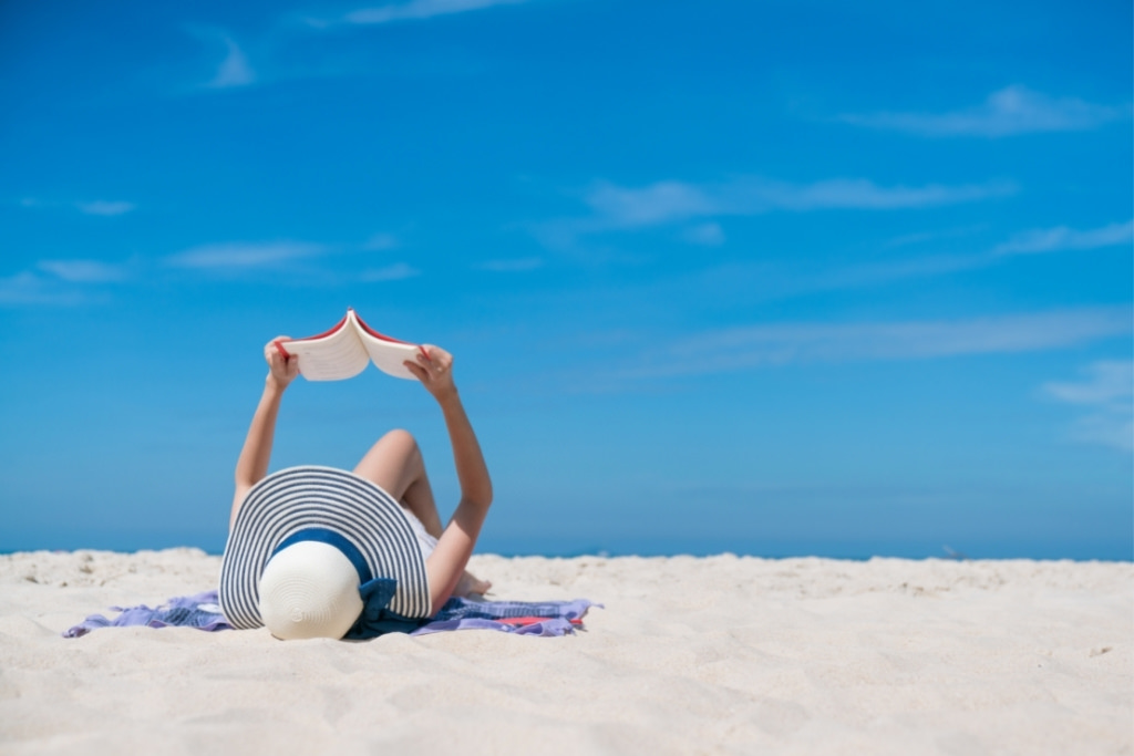 girl reading book on the beach