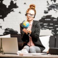 woman holding a globe with laptop on table