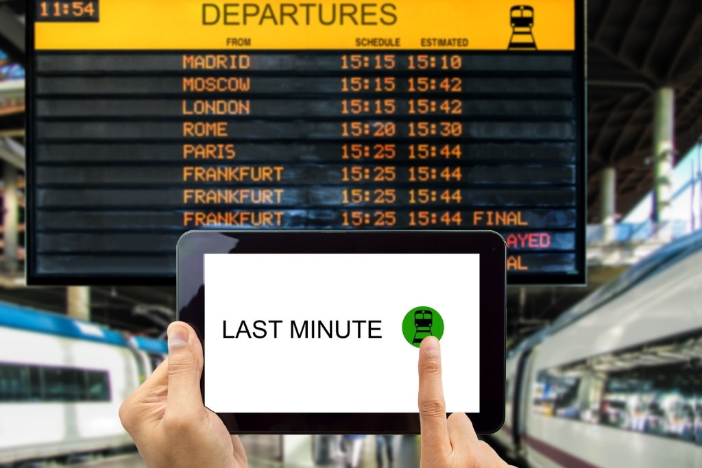 train station with person holding tablet with last minute deals on it