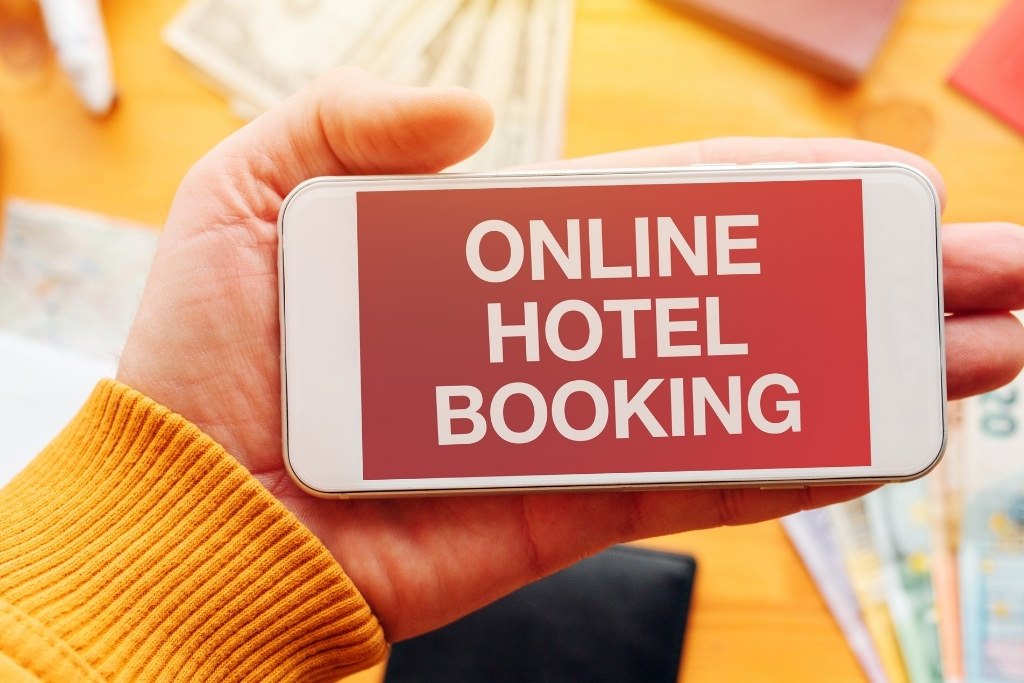 girl holding cell phone with the words online hotel booking on it