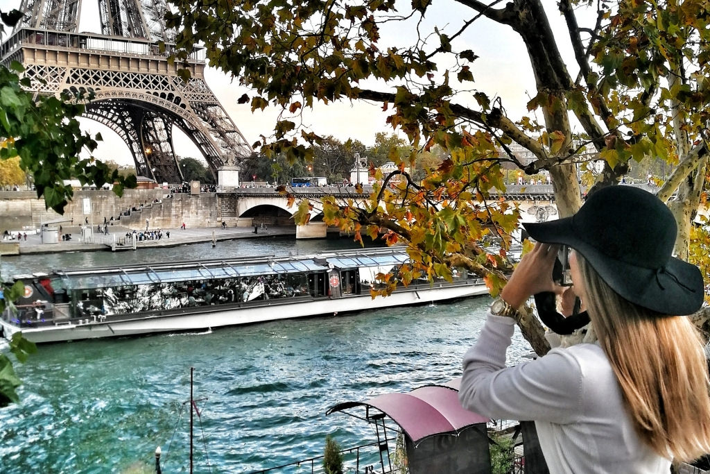 woman taking photo of the eiffel tower sitting near the seine river