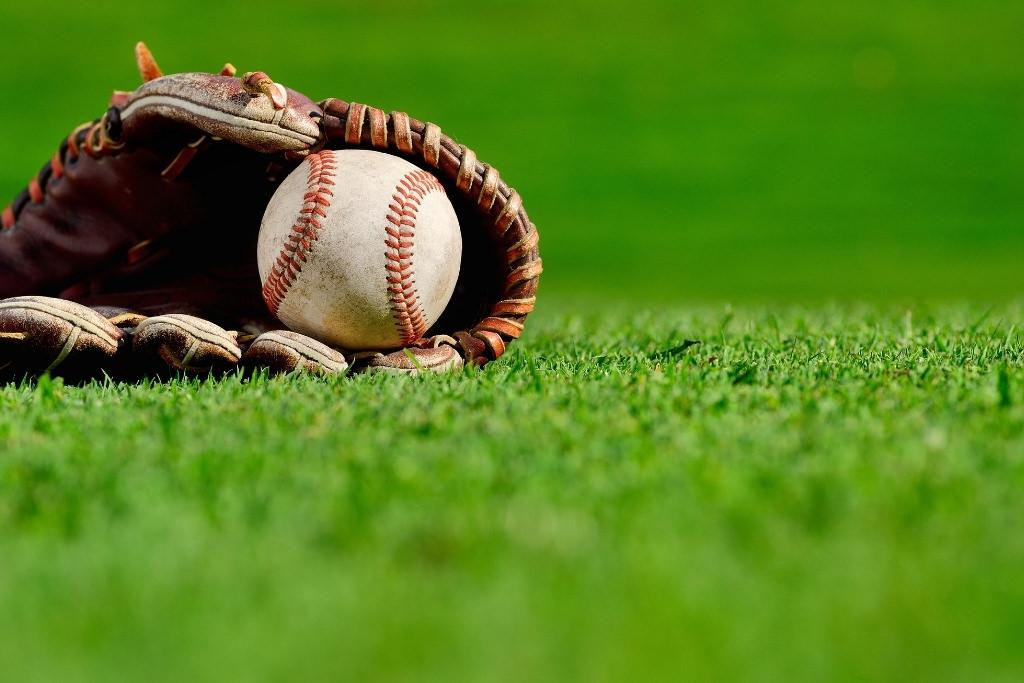 baseball and glove on grass field