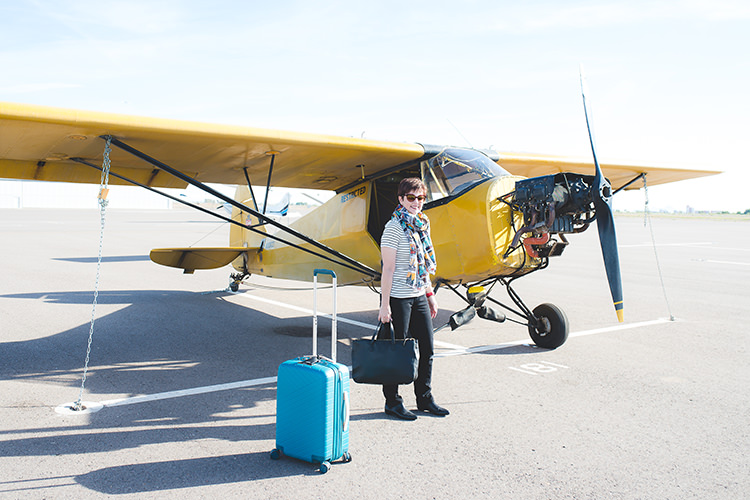 Andi in front of airplane with suitcase and bad