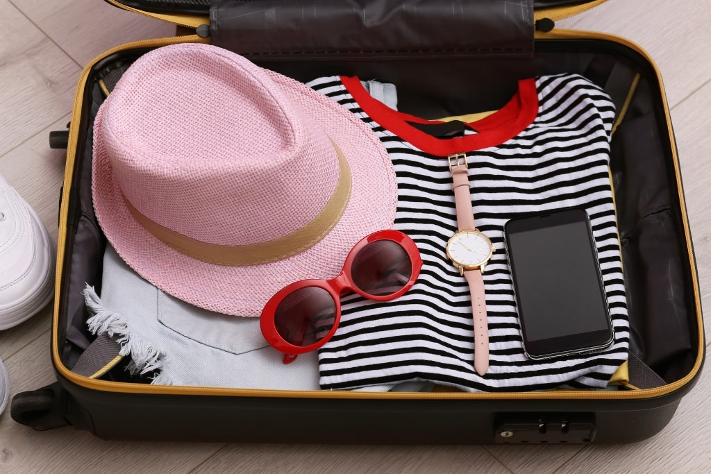 suitcase with pink hat and red sunglasses