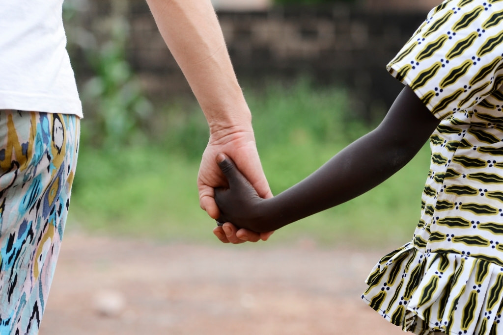 woman holding childs hand