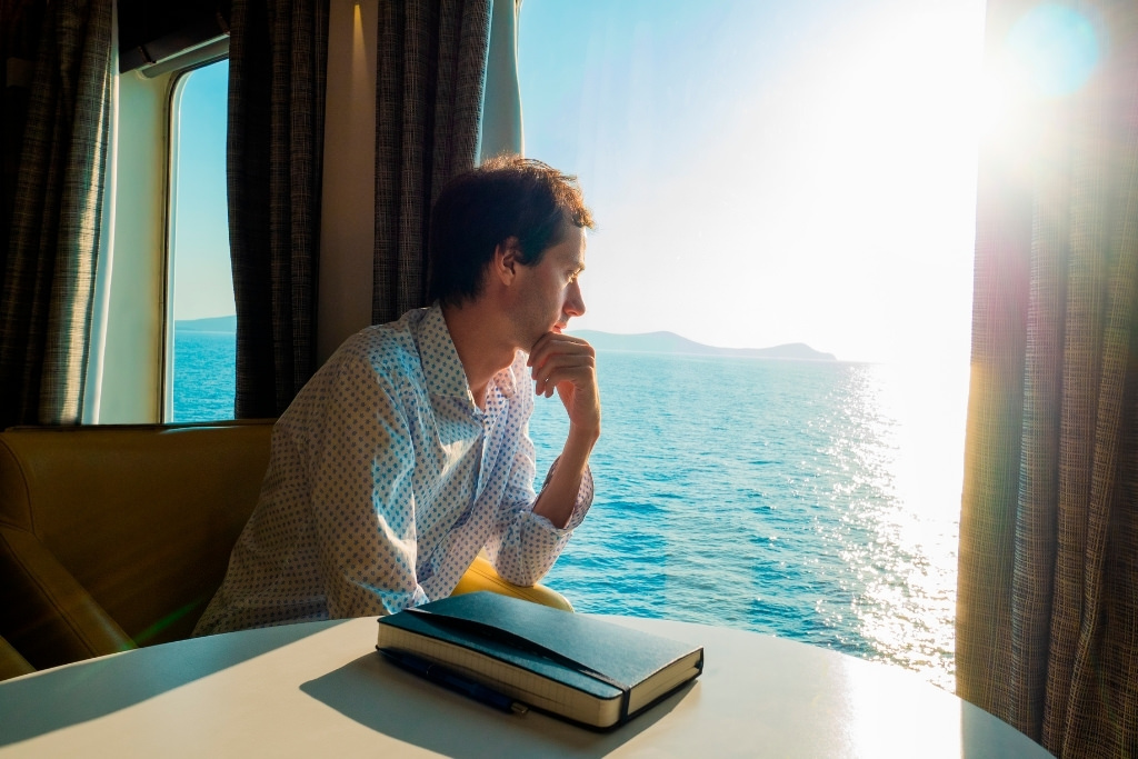 man looking out cruise window