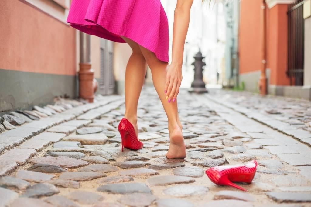 women in red high heels on cobblestone street