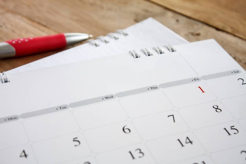 paper calendar on wood table with red pen