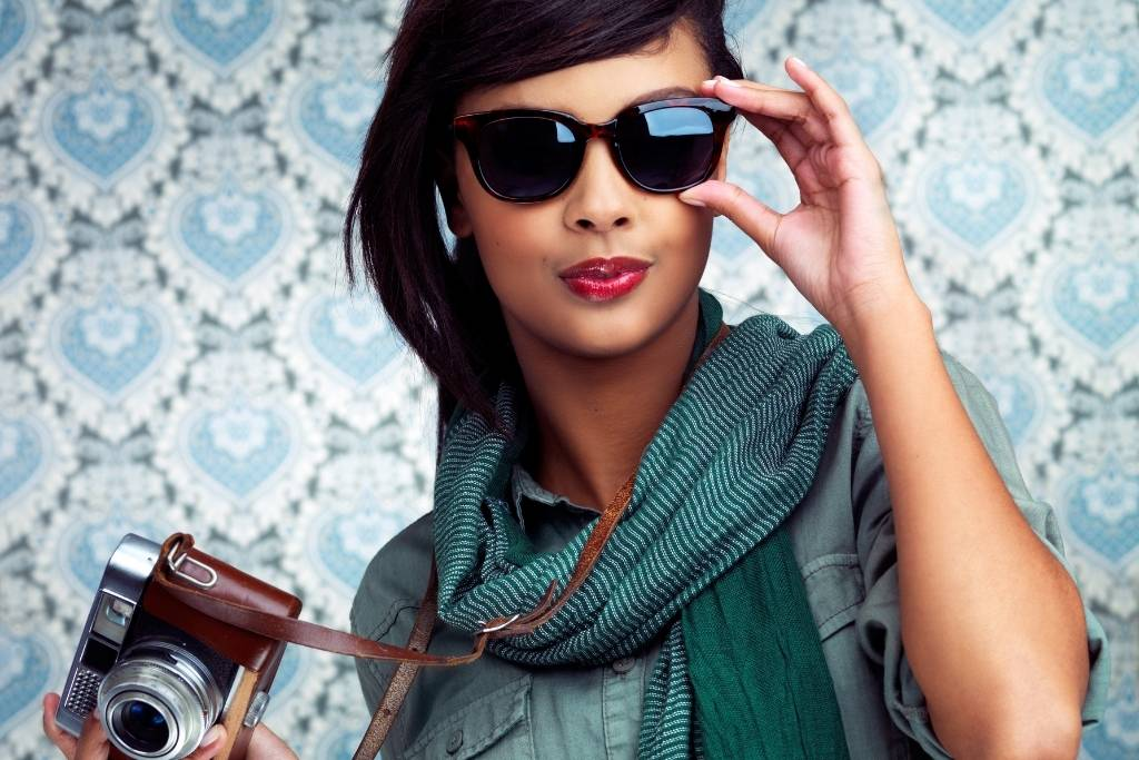 girl with camera in sunglasses shirt and scarf