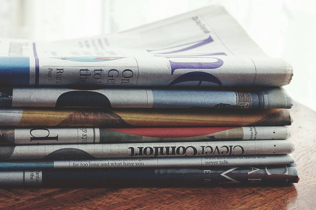 stacked newspapers on wood table